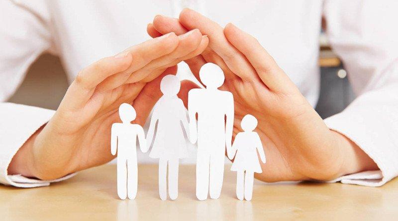 Weibliche Hände schützen eine Familie aus Papier
